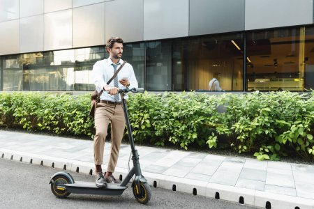 Photo for Full length of businessman holding smartphone while standing near e-scooter, plants and building - Royalty Free Image