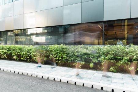 Photo pour Flou de mouvement des gens marchant dans la rue urbaine près de bâtiments modernes et de plantes vertes - image libre de droit