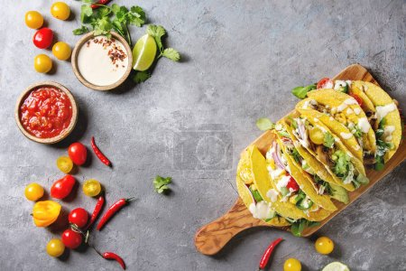 Photo for Variety of vegetarian corn tacos with vegetables, green salad, chili pepper served on olive wood board with tomato, cream sauces with ingredients above over grey texture background. Top view, space. - Royalty Free Image