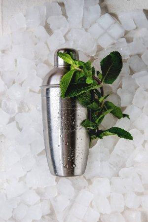 Cocktail making concept. Silver shaker with bundle of fresh mint over crushed ice cubes. Flat lay, space.