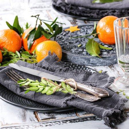 Photo pour Décorations de table de Noël avec des feuilles de mandarines clémentines et des branches vertes sur panneau orné noir. Verre et assiette vides avec couverts et serviette textile sur une table en bois blanc. Image carrée - image libre de droit