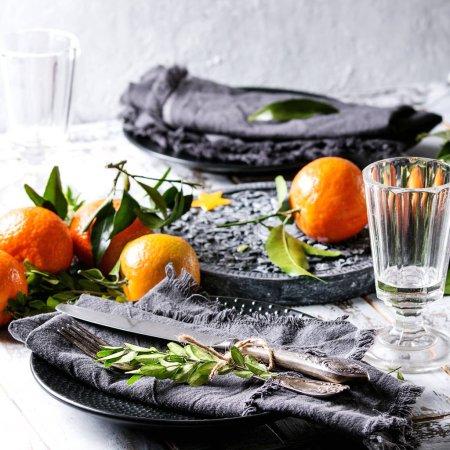 Photo pour Décorations de table de Noël avec clémentines ou mandarines aux feuilles et branches vertes sur panneau orné noir. Verre vide, assiette, couverts et serviette en tissu sur une table à planches en bois blanc. Image carrée - image libre de droit