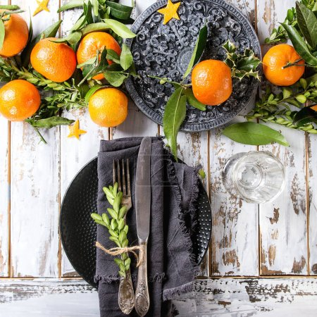Photo for Christmas table decorations with clementines or tangerines with leaves and branches on black ornate board. Empty plate with cutlery and textile napkin over white wooden plank table. Top view. Square image - Royalty Free Image