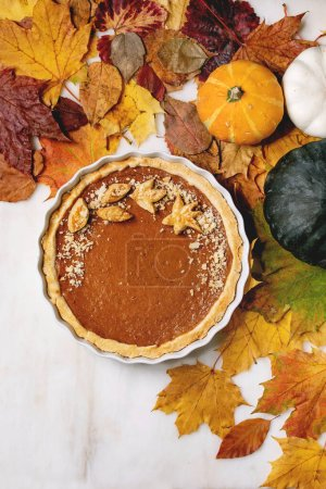 Photo for Traditional homemade autumn pumpkin pie for Thanksgiving or Halloween dinner served in ceramic dish with pumpkins and yellow autumn leaves over white marble background. Flat lay, space - Royalty Free Image