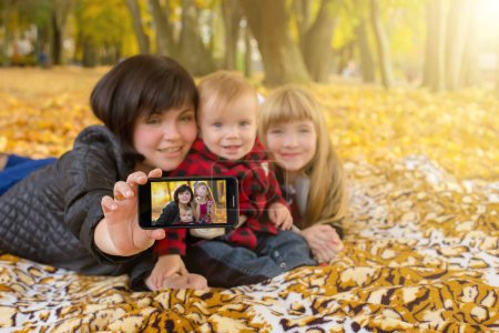 happy family sitting on grass in autumn park ant taking selfie