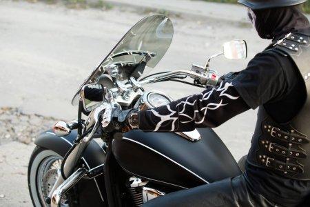 biker sitting on big chopper bike. back view