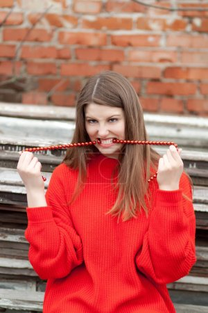 young woman in red sweater posing near brick wall