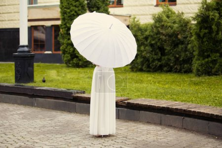Beautiful happy bride in white dress with decorative umbrella against background green nature. In a summer park