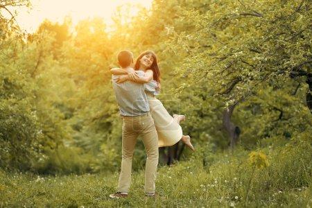 Photo pour Couple heureux hugging en parc d'été au coucher du soleil - image libre de droit