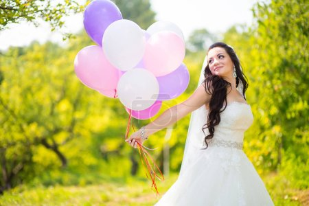 Photo for Happy stunning bride in dress wit colorful ballons in green park - Royalty Free Image