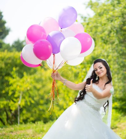 Foto de Feliz novia impresionante vestido de globos coloridos de ingenio en parque verde y mostrar buena señal con el dedo - Imagen libre de derechos