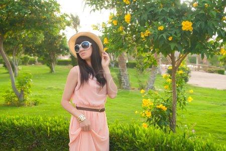 Mujer de primavera en vestido de verano de pie en park .Playful y beaut