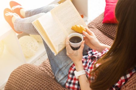 Photo for Woman sitting on the sofa reading a book holding her coffee mug in living room at home - Royalty Free Image