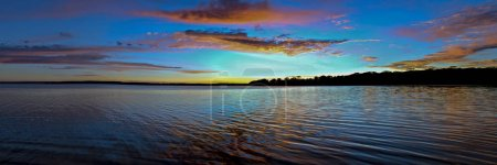 A spectacular inspirational brightly coloured red and blue cloudy sea water tropical panoramic sunrise seascape with ocean water reflections. Queensland, Australia.