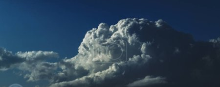 A spectacular inspirational brightly coloured atmospheric cloudy sky cloudscape featuring a  Cumulonimbus cloud formation in a mid blue sky. New South Wales, Australia.