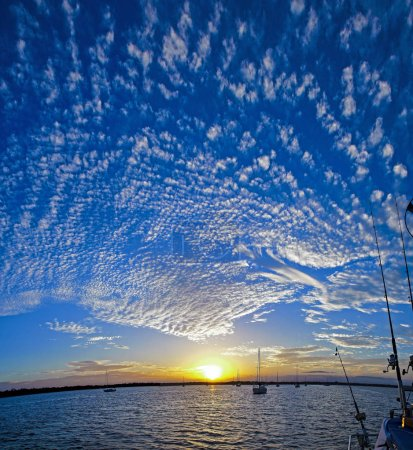 A spectacular inspirational brightly coloured atmospheric cloudy sky cloudscape featuring a Altocumulus cloud formation in a mid blue sky. New South Wales, Australia.