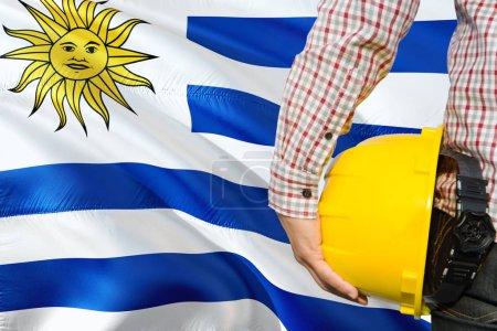Photo pour Uruguayan Engineer tient un casque de sécurité jaune avec un fond de drapeau uruguayen. Concept de construction et de construction . - image libre de droit