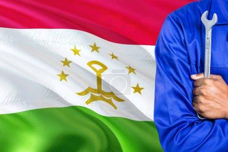 Photo pour Le mécanicien tadjik en uniforme bleu tient la clé contre le drapeau du Tadjikistan. Technicien des bras croisés . - image libre de droit
