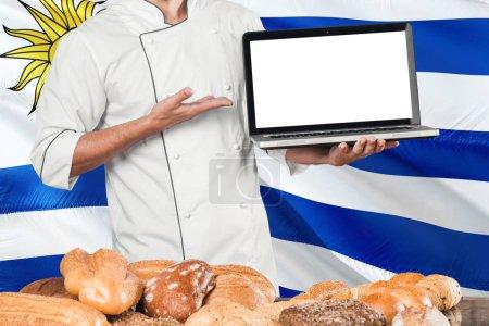 Photo pour Baker uruguayen tenant ordinateur portable sur drapeau de l'Uruguay et fond de pains. Chef portant uniforme pointant écran vierge pour l'espace de copie . - image libre de droit