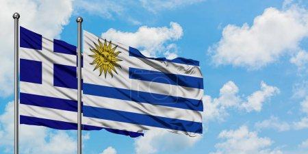 Photo pour Drapeau de la Grèce et de l'Uruguay agitant dans le vent contre ciel bleu nuageux blanc ensemble. Concept de diplomatie, relations internationales . - image libre de droit