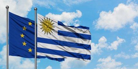 Photo pour Drapeau de l'Union européenne et de l'Uruguay agitant dans le vent contre le ciel bleu nuageux blanc ensemble. Concept de diplomatie, relations internationales . - image libre de droit