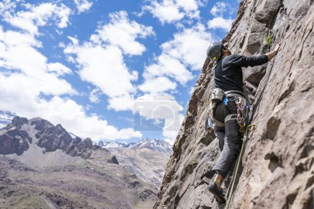 Photo for The last movements to reach the summit by a male climber. Rock climbing inside Andes mountains and valleys at Cajon del Maipo, an amazing place to enjoy rock climbing and mountaineering sports, Chile - Royalty Free Image