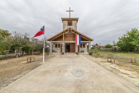 Photo pour Vue de l'église en bois avec des drapeaux parmi le paysage étonnant et vert à Cobquecura, Chili - image libre de droit