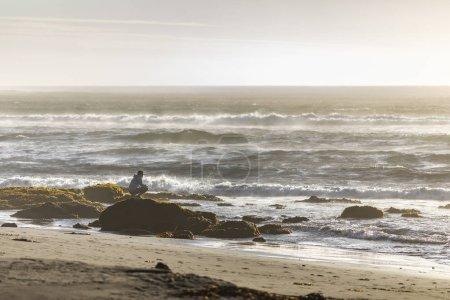 Photo pour Homme assis sur la pierre et regardant l'océan Pacifique avec des vagues s'écrasant sur la côte sablonneuse - image libre de droit