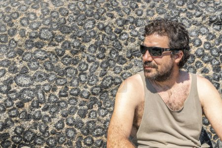 Photo for Handsome young man with beard sitting near texture background of stone leaves in the sand - Royalty Free Image