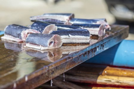 Photo for Some slices of fresh fish above a wooden table inside a fishermen boat. Traditional healthy food tempting our eyes with it freshness. A delicious freshly caught swordfish - Royalty Free Image