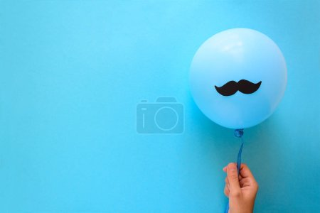 Hand holding blue balloon with a paper mustache on blue paper background. Cut out style. Movember