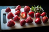 A white cutting board filled with hulled strawberries.