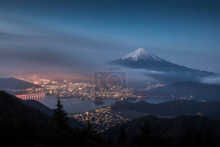 Night landscape of Mountain Fuji with cloudy sky and Kawaguchiko lake seen from Shindo toge view point.