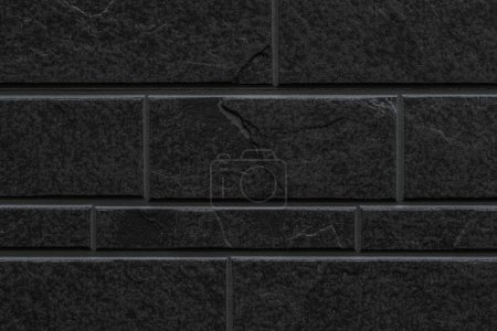 seamless black stone tile wall pattern and background