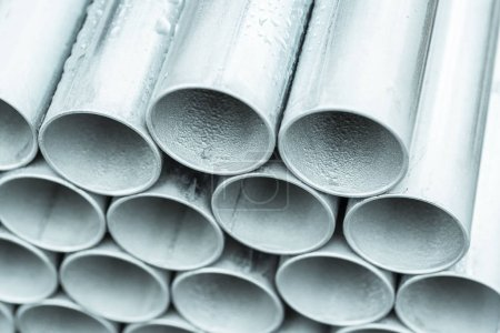 Closeup of stack of metal pipes on factory