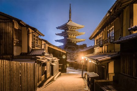 Japanese pagoda and old houses in snow falling day at Kyoto prefecture