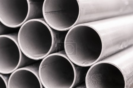 Close-up stack of metal pipes industrial background