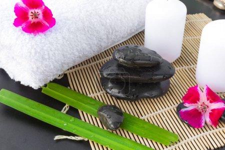 Photo pour Bougies, fleurs, pierres sur fond de verdure pour le massage spa détente - image libre de droit