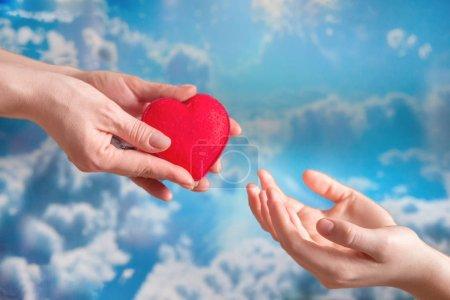 Hände reichen das Herz an das Kind, kümmern sich um den Tag des Spenders gegen den Himmel, hoffen auf Gesundheit, auf Organspende