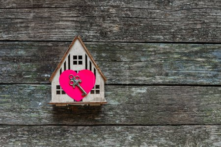 Photo for Concept of a new home with a heart and key on a wooden background with copy space, a gift for Valentine's Day, the idea of a family of love and comfort - Royalty Free Image