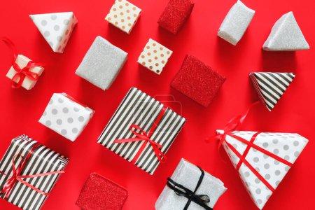 Photo pour Plat Lay Noël ou fond de fête avec des boîtes-cadeaux, rubans, décorations en argent, rouge et noir couleurs. Couché plat, vue sur le dessus, Noël sur fond rouge - image libre de droit