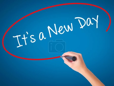 Photo for Women Hand writing It's a New Day with black marker on visual screen. Isolated on blue. Business, technology, internet concept. Stock Photo - Royalty Free Image