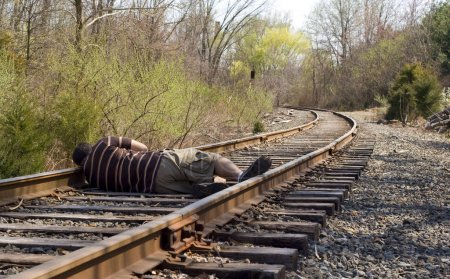Photo for A man laying on the railroad tracks. Not exactly the smartest thing to do. - Royalty Free Image