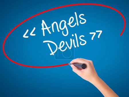 Photo for Women Hand writing Angels - Devils with black marker on visual screen. Isolated on blue. Business, technology, internet concept. Stock Photo - Royalty Free Image