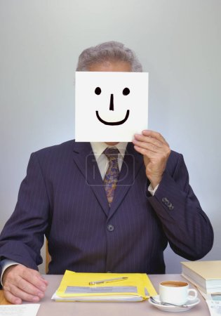 Photo for A businessman sits at his desk, holding a home-made smiley mask in front of his face. Look ... I'm happy ... really! - Royalty Free Image