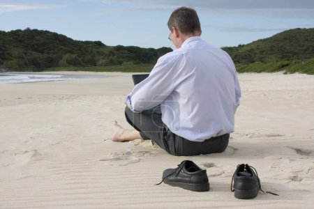 Photo for Businessman working with his laptop while sitting barefoot on the beach. - Royalty Free Image