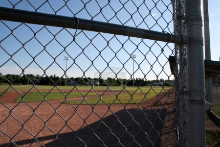 Photo for A view from behind the fence at a small baseball field. - Royalty Free Image