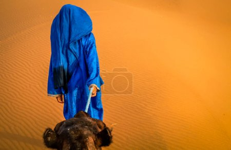 Photo for Berber leading a camel into the stunning sand dunes of Sahara desert in Merzouga, Morocco - Royalty Free Image
