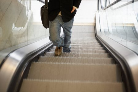 Photo for Teenager walking up in escalator, low section - Royalty Free Image
