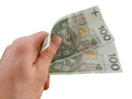 Men's hand holding a hundret zloty bills